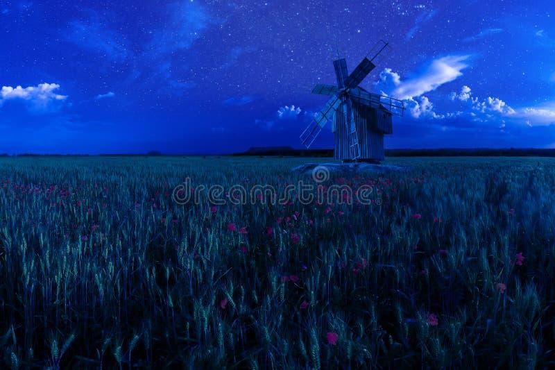 Старая ветрянка на пшеничном поле ночи стоковая фотография