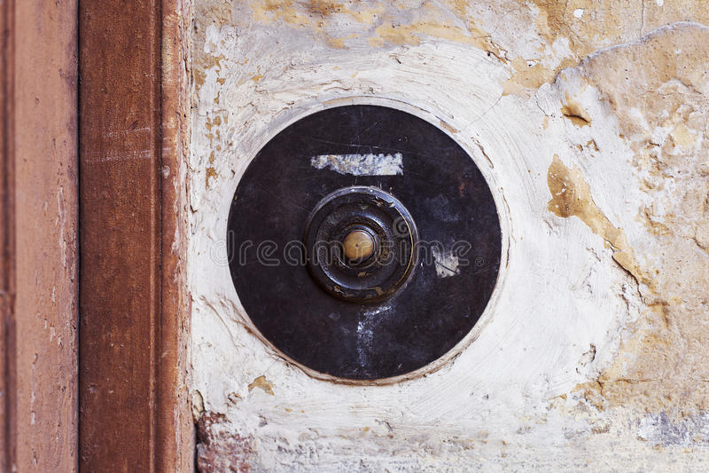 Старая винтажная кнопка дверного звонка на стене grunge стоковое изображение