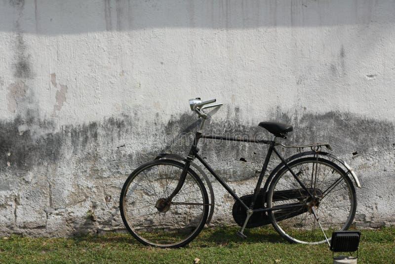 Старая винтажная склонность велосипеда против стены стоковое фото