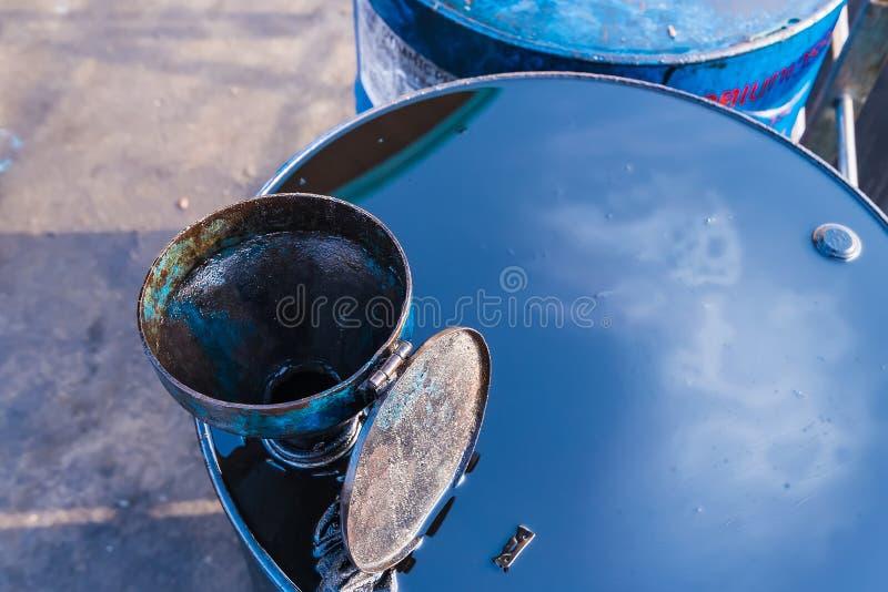 Старая воронка масла на ржавых бочонках масла металла на верфи r r стоковые фотографии rf