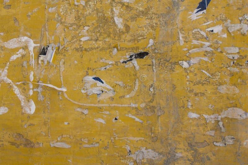 Старая грязная желтая бетонная стена с повреждением, царапинами, серыми пятнами краски и обмылками сорванных бумажных объявлений  стоковое изображение