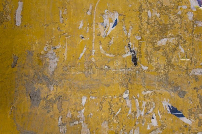 Старая грязная желтая бетонная стена с повреждениями, серые пятна краски и обмылки сорванных бумажных объявлений E стоковые изображения rf