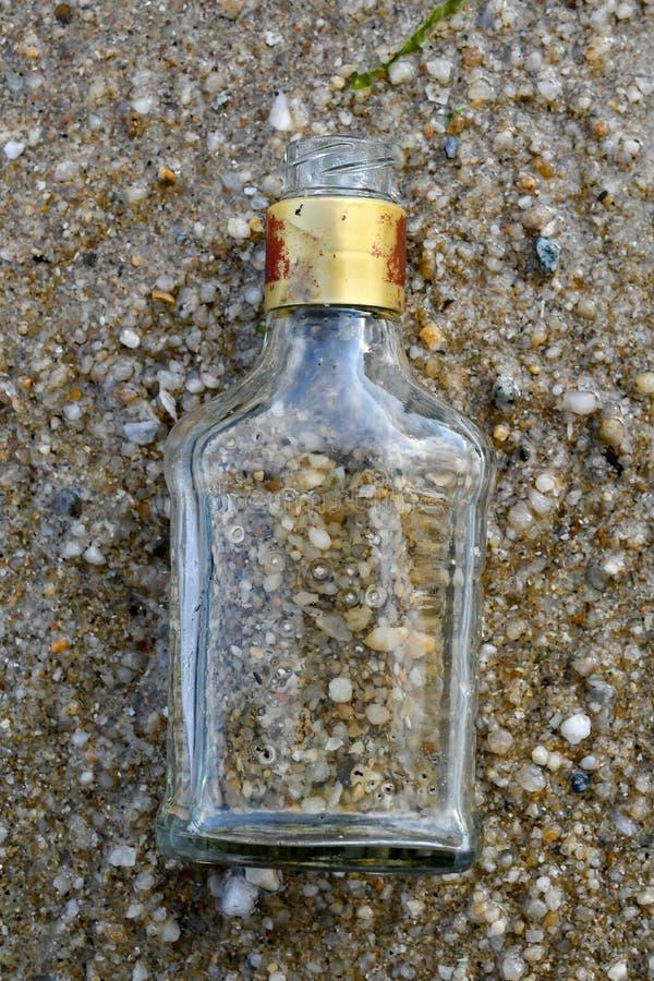Старая грязная стеклянная бутылка на песчаном пляже стоковые изображения rf