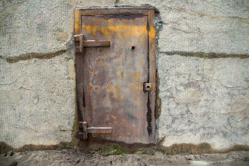 Старая дверь металла в бетонной стене стоковое фото rf