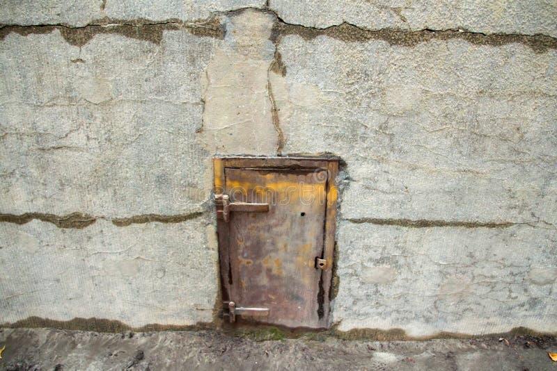 Старая дверь металла в бетонной стене стоковая фотография