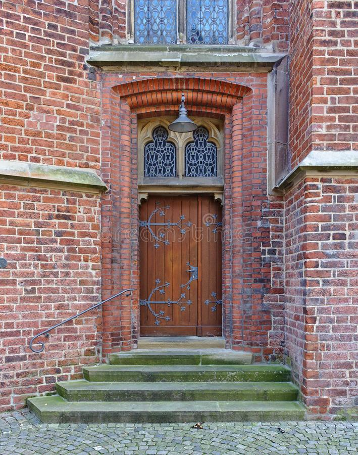 Старая деревянная дверь в кирпичной стене с железными штуцерами, шагами и орнаментальными окнами стоковые изображения rf