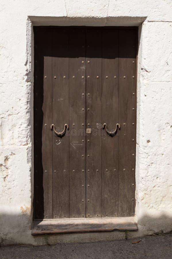 старая деревянная дверь с железными ручками двери в полдень стоковые изображения