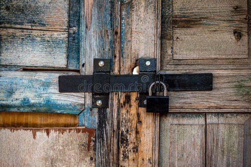 Старая деревянная дверь с тяжелым замком стоковые фото