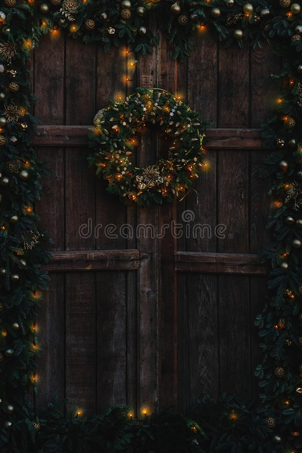 Старая деревянная дверь украшенная с гирляндой и венком рождества, и с теплыми светами стоковая фотография rf