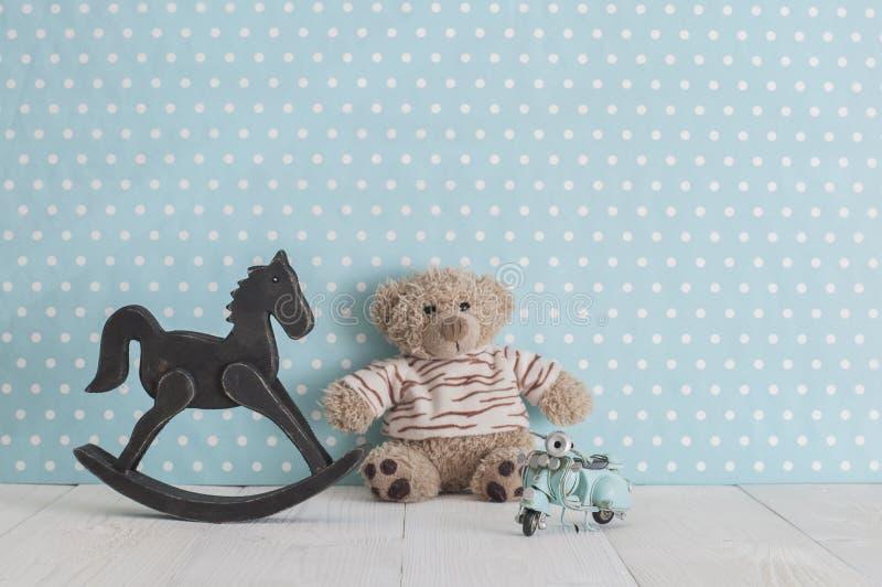 Старая деревянная кресло-качалка лошади игрушки, плюшевый мишка и голубой год сбора винограда стоковые фото