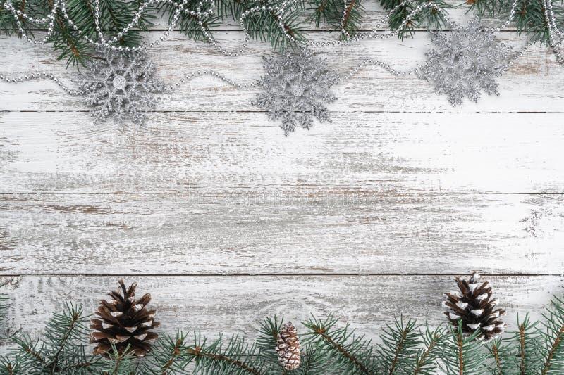 Старая деревянная предпосылка рождества Гирлянды и снежинки разветвляет ель конусов Поздравительная открытка Xmas Взгляд сверху стоковые изображения rf