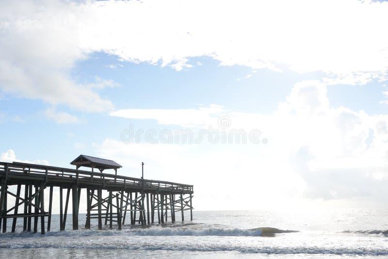 Старая деревянная пристань позволяет рыболовам доступу к более глубокой воде стоковое фото rf