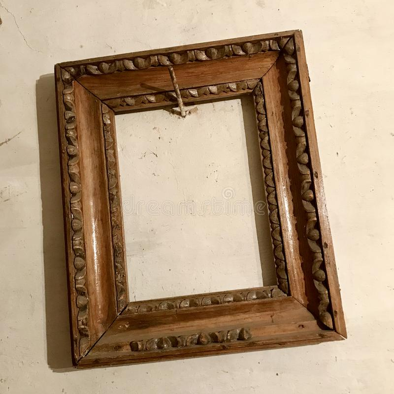 Старая деревянная пустая рамка фото вися на стене пригвоздила ржавый стальной ноготь стоковое фото