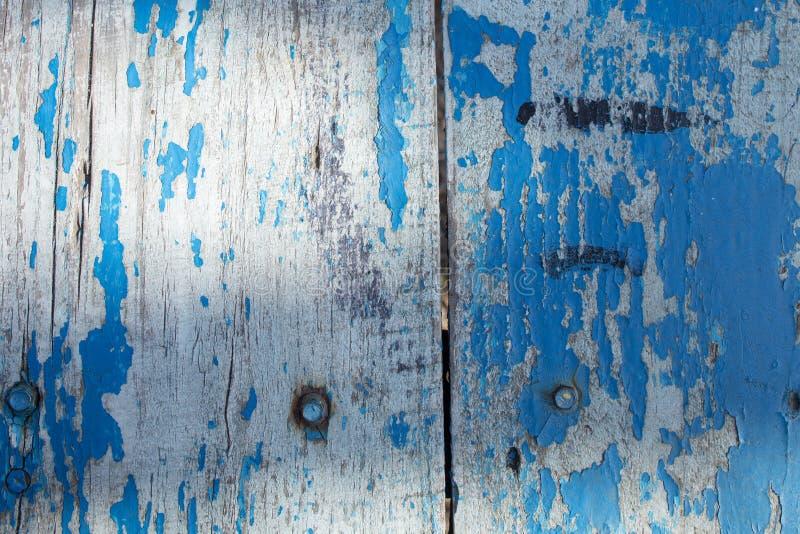 Старая деревянная серая загородка сделанная планок со слезать голубую краску стоковое изображение