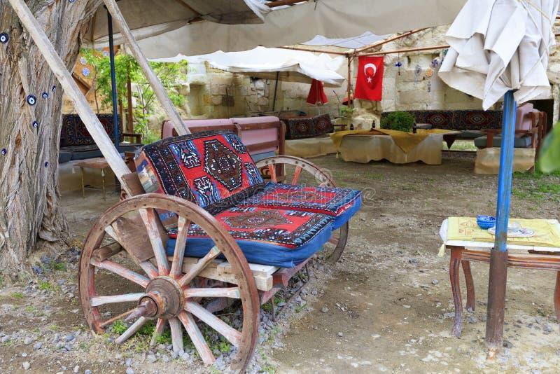 Старая деревянная тележка как мягкий стул на таблице во дворе  турецкого двора стоковое изображение rf