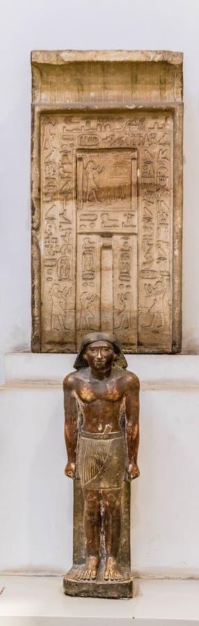 Старая египетская статуя и блок камня с иероглифами стоковые фото