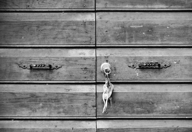 Старая деревянная дверь при ключевые цепи вися на двери стоковые фото