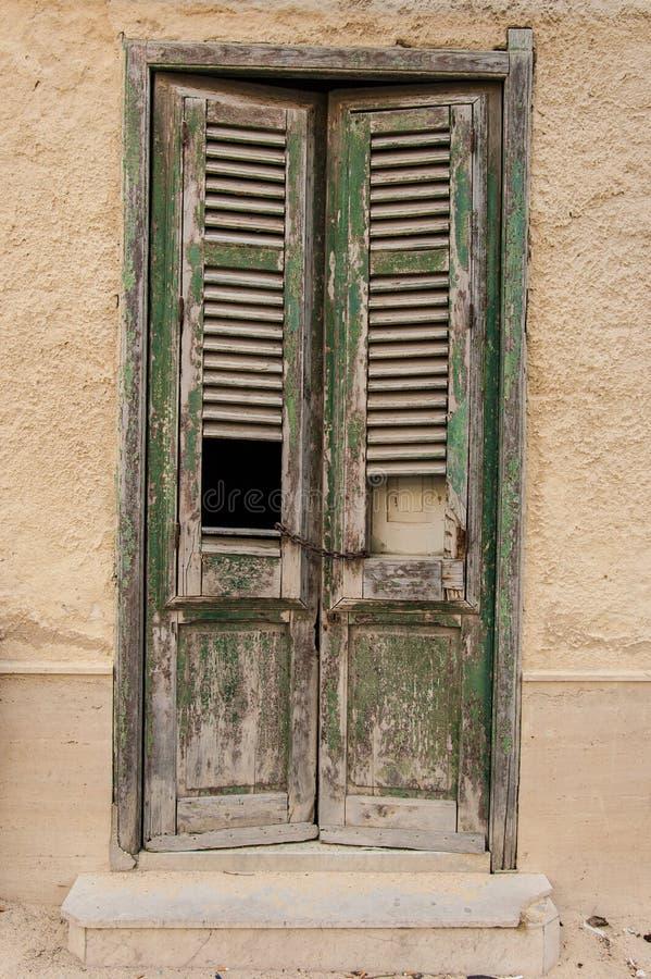 Старая деревянная дверь с квадратным отверстием и ржавой цепью как шкафчик стоковые фото
