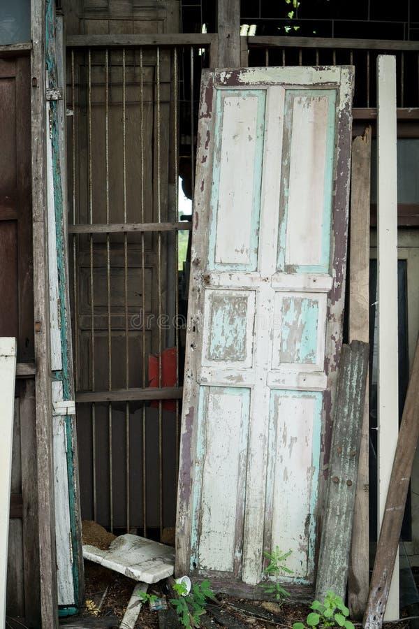 Старая деревянная склонность двери против старой ржавой стены металлического стержня стоковая фотография
