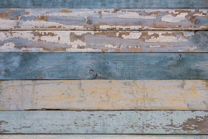 Старая желтая голубая белая деревянная загородка стены деревянных доск со слезать краску горизонтальные прямые E стоковые изображения rf