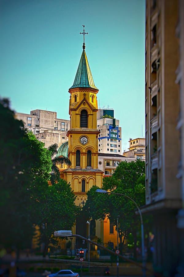 Старая желтая церковь между зданиями стоковое фото