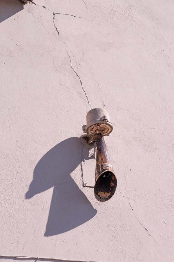 Старая заржаветая сирена на стене дома стоковая фотография rf