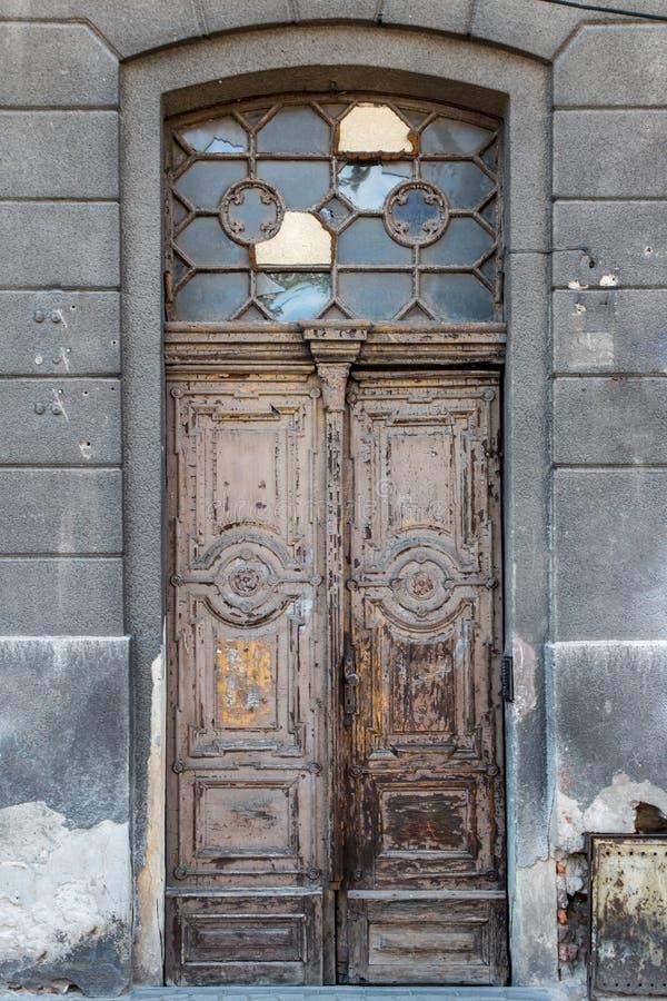 Старая затрапезная винтажная дверь с сломленными окнами стоковые изображения