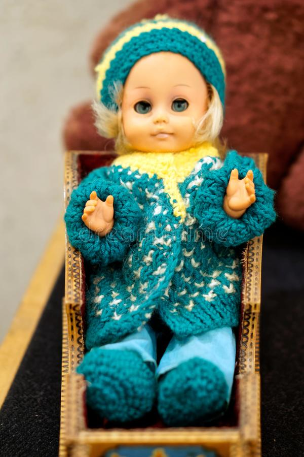 Старая игрушка винтажная кукла с голубыми глазами в шерстяной шляпе сидя в санях Вопрос от прошлой малой глубины поля стоковые изображения rf
