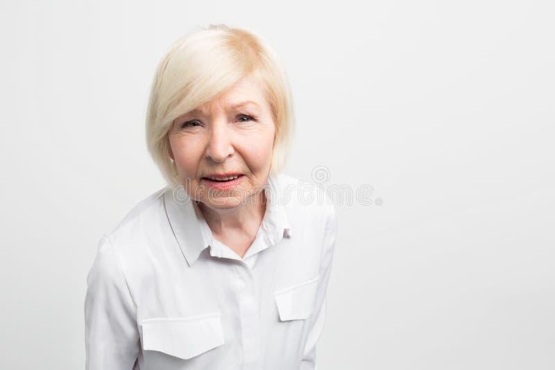 Старая и каверзная женщина очень внимательна к деталям Она пробует проверить все здесь Эта бабушка очень стоковые изображения