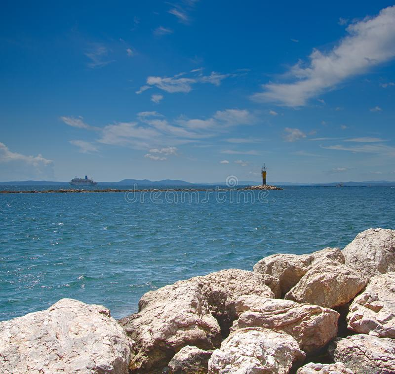 Старая каменная пристань в море и маяке стоковое фото