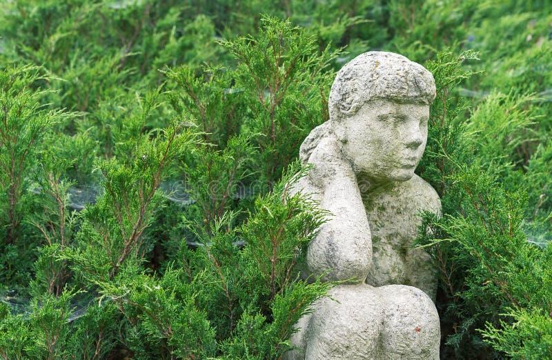 Старая каменная статуя сидя девушки среди зеленых кустарников стоковое изображение