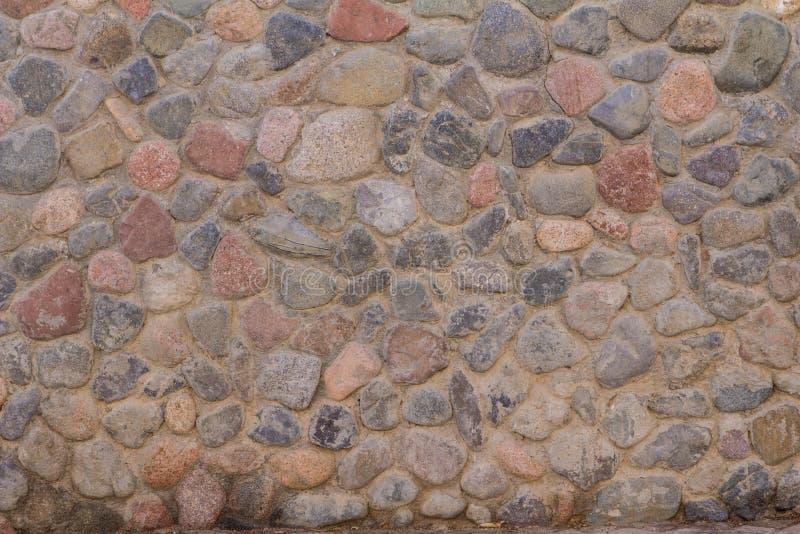 Старая каменная стена круглых камней и серого цемента стоковое фото