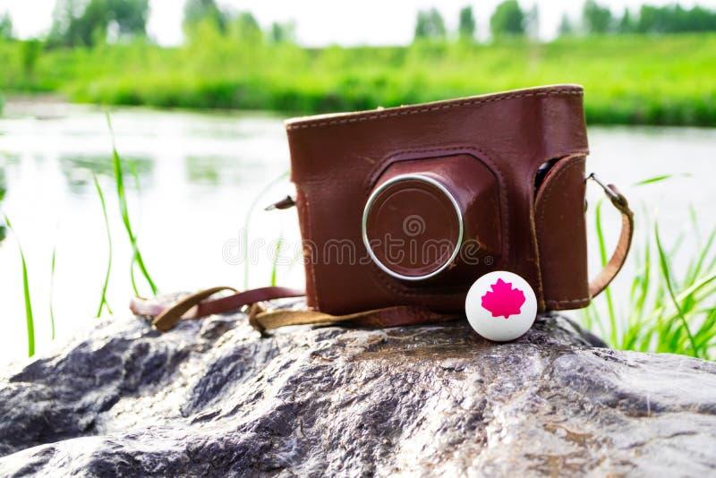 Старая камера в коричневом случае и шарик с символом Канады стоковые фото