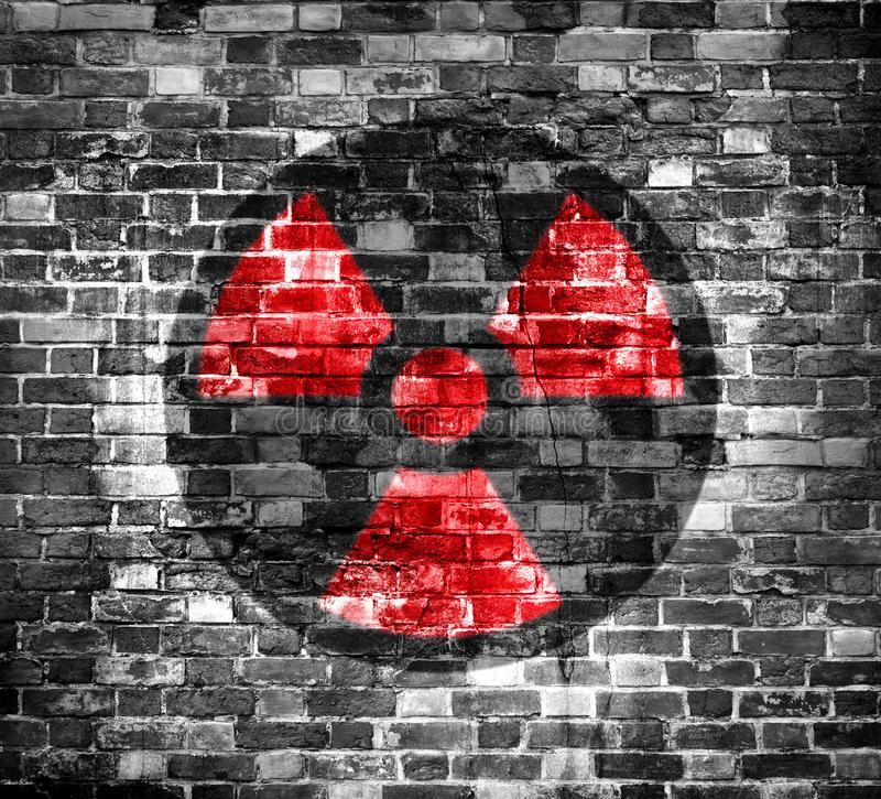 Старая кирпичная стена с символом радиации предупреждающим покрашенным на ем перевод 3D или иллюстрация ( стоковое фото rf