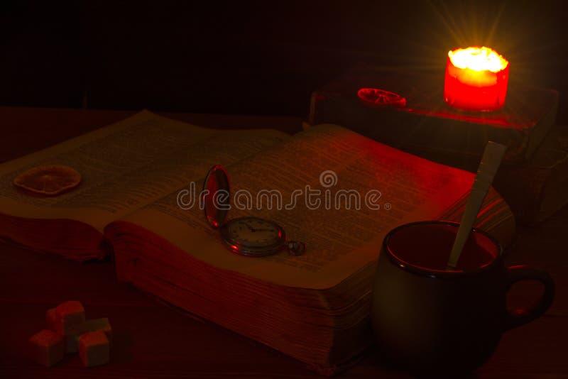 Старая книга на таблице Открытая библия на таблице стародедовский ключ Горящая свеча над библией освещает свои страницы mu стоковые фото