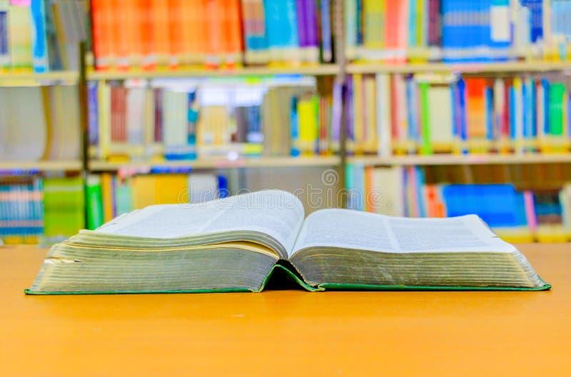 старая книга открытая в школьной библиотеке на деревянном столе расплывчатая предпосылка книжных полок стоковые изображения