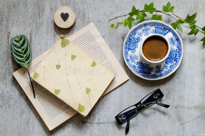 Старая книга, стекла, чашка кофе и конверт на таблице жизни сбор винограда все еще стоковое изображение