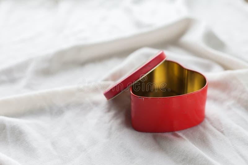 Старая коробка в форме сердца на белой предпосылке, на белой ткани, в желейных бобах коробки красных сладостных, день ` s валенти стоковые фотографии rf