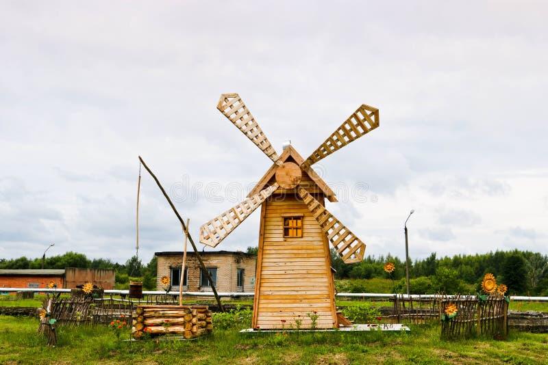 Старая красивая деревянная заготовка для заготовки зерна Традиционный миллер с большими лопатками в деревне с колодцем стоковое изображение