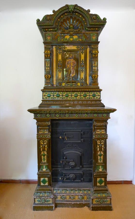 Старая, красиво украшенная изразцовая печь с вставкой черного листового железа против светлой предпосылки стоковые изображения