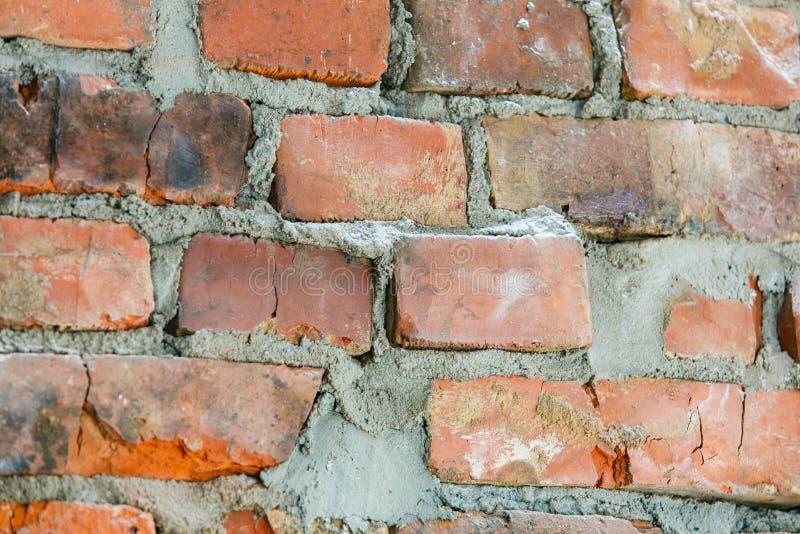 Старая красная кирпичная стена в предпосылке улицы стоковое фото