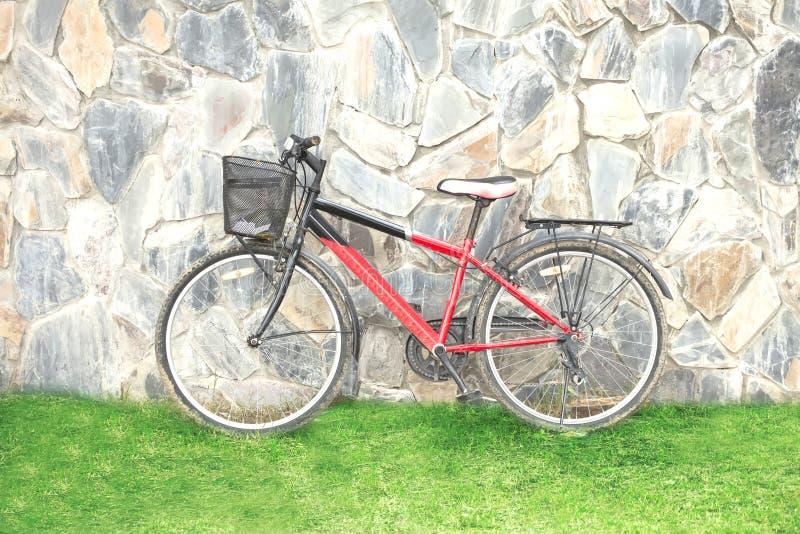 Старая красная склонность велосипеда против стены стоковое фото rf