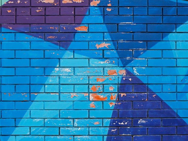 Старая красочная голубая краска с отказами на кирпичной стене стоковые фото
