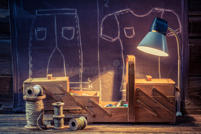Старая мастерская портноя с иглами, потоками и материалами иллюстрация штока
