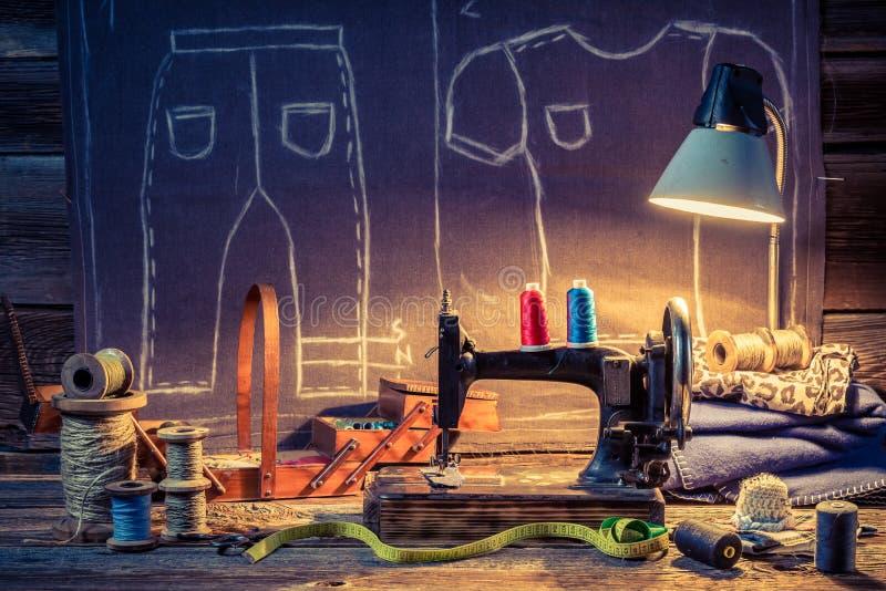 Старая мастерская портноя с швейной машиной и тканью иллюстрация вектора
