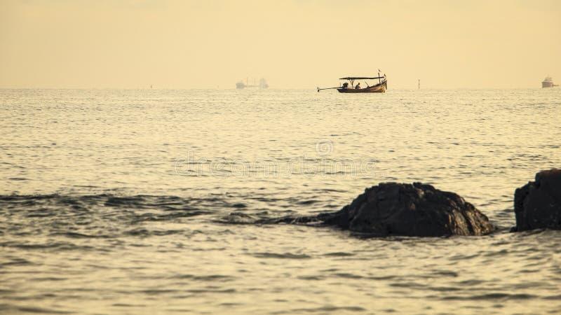 Старая малая рыбацкая лодка сделанная от деревянного плавания в море которое имеет буровую вышку как предпосылка и скалистый как  стоковое фото rf