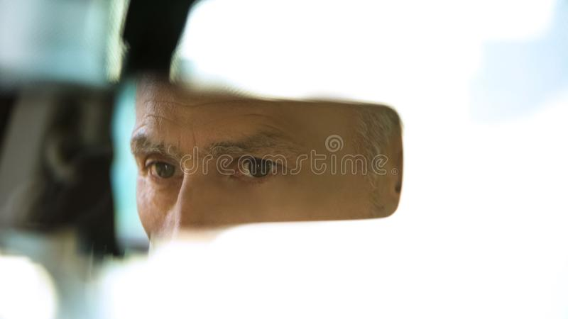 Старая мужская сторона отражая в зеркале заднего вида, водителе такси, безопасности дорожного движения, автомобиле стоковое фото