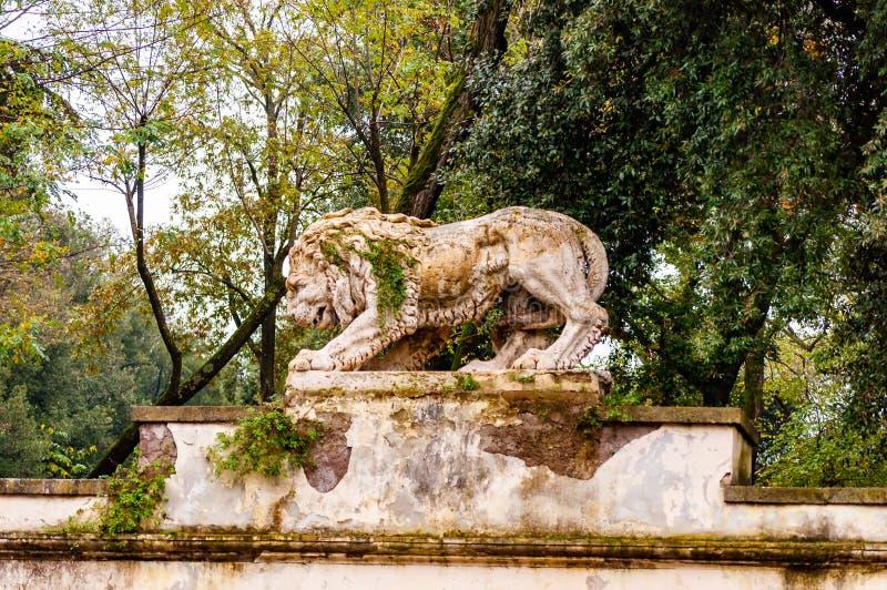 Старая мшистая перерастанная статуя скульптуры камня льва в парке Borghese на пути к вилле Borghese стоковые изображения rf
