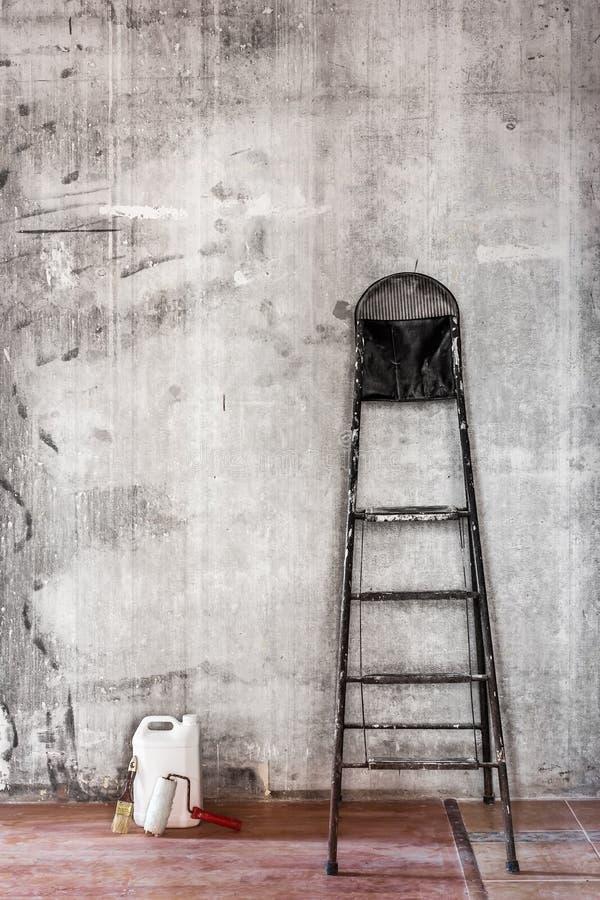 Старая пакостная бетонная стена в ремонтировать комнату с stepladder и к стоковое фото