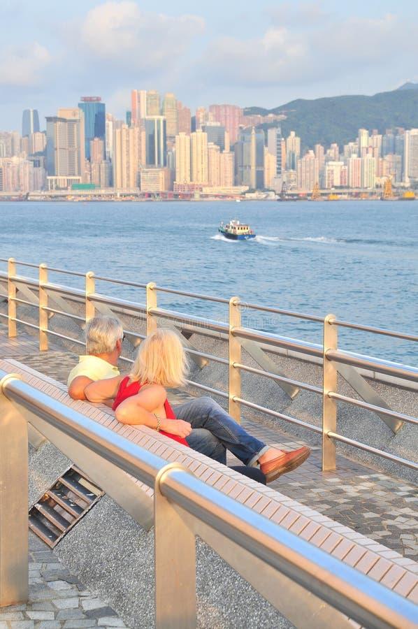 старая пара сидит на порте Гонконга стоковая фотография rf